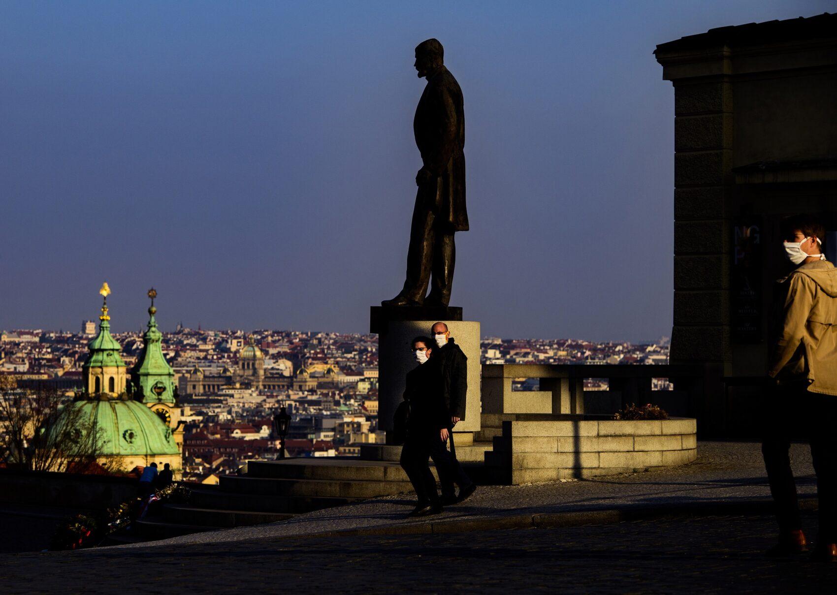 Pohled na sochu Tomáše Masaryka na pozadí večerní Prahy, kolem níž procházejí lidé v rouškách
