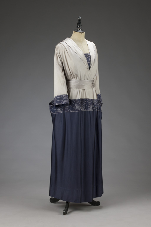 Šaty se světlým vršlem a modrou sukní, v pase přepásané šerpou