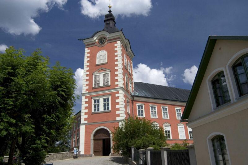 Zámek v Kamenici nad Lipou má vstupní věž a červenou fasádu