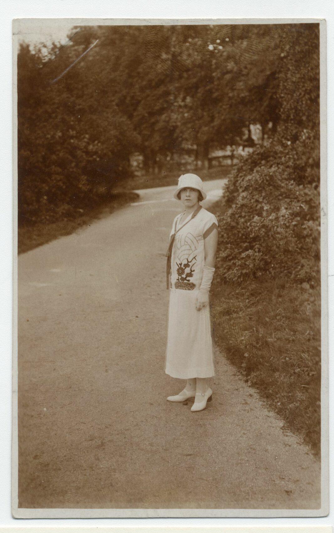 Fotografie mladé ženy v dlouhých světlých šatech s kloboučkem a vysokými rukavicemi