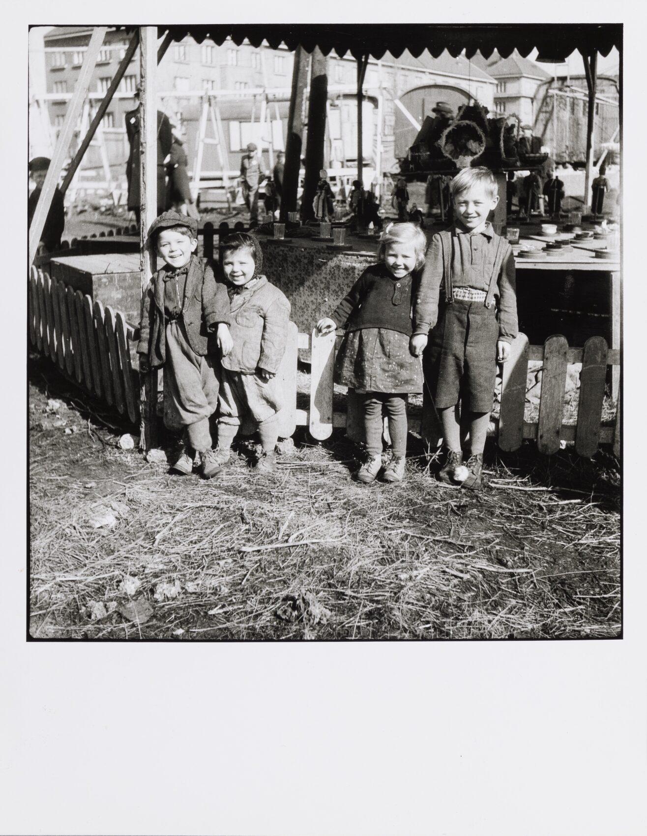 Čtyři malé rozesmáté děti stojí před vesnickou poutí