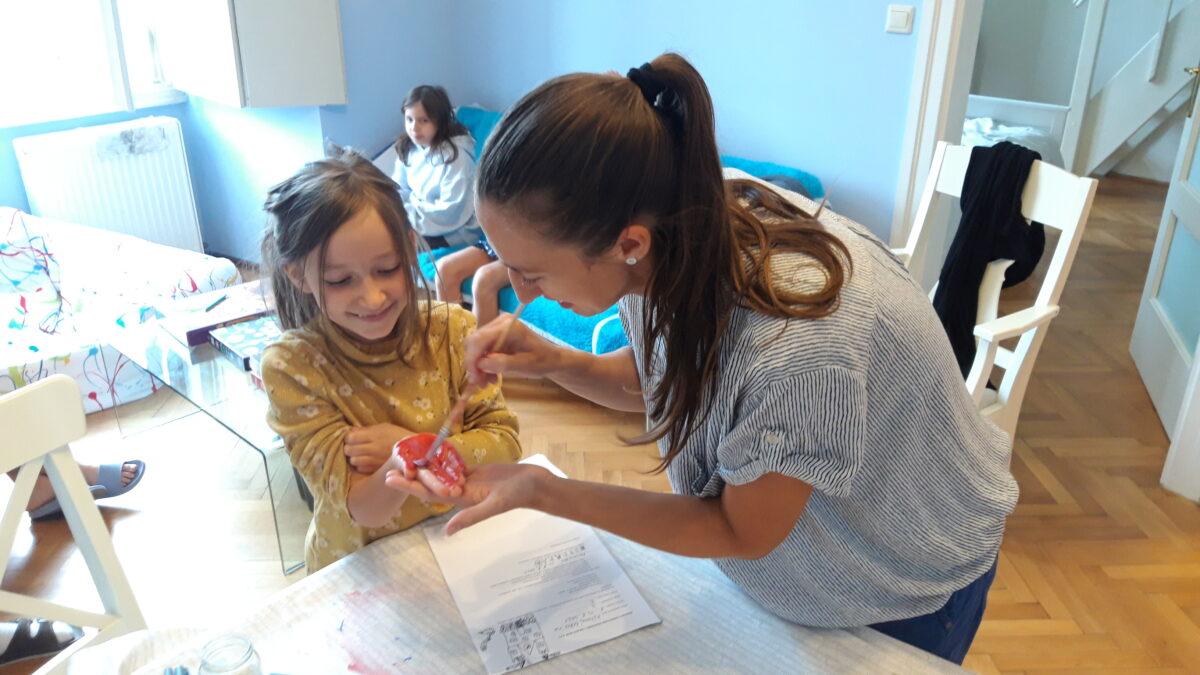 Žena maluje holčičce dlaň barvou