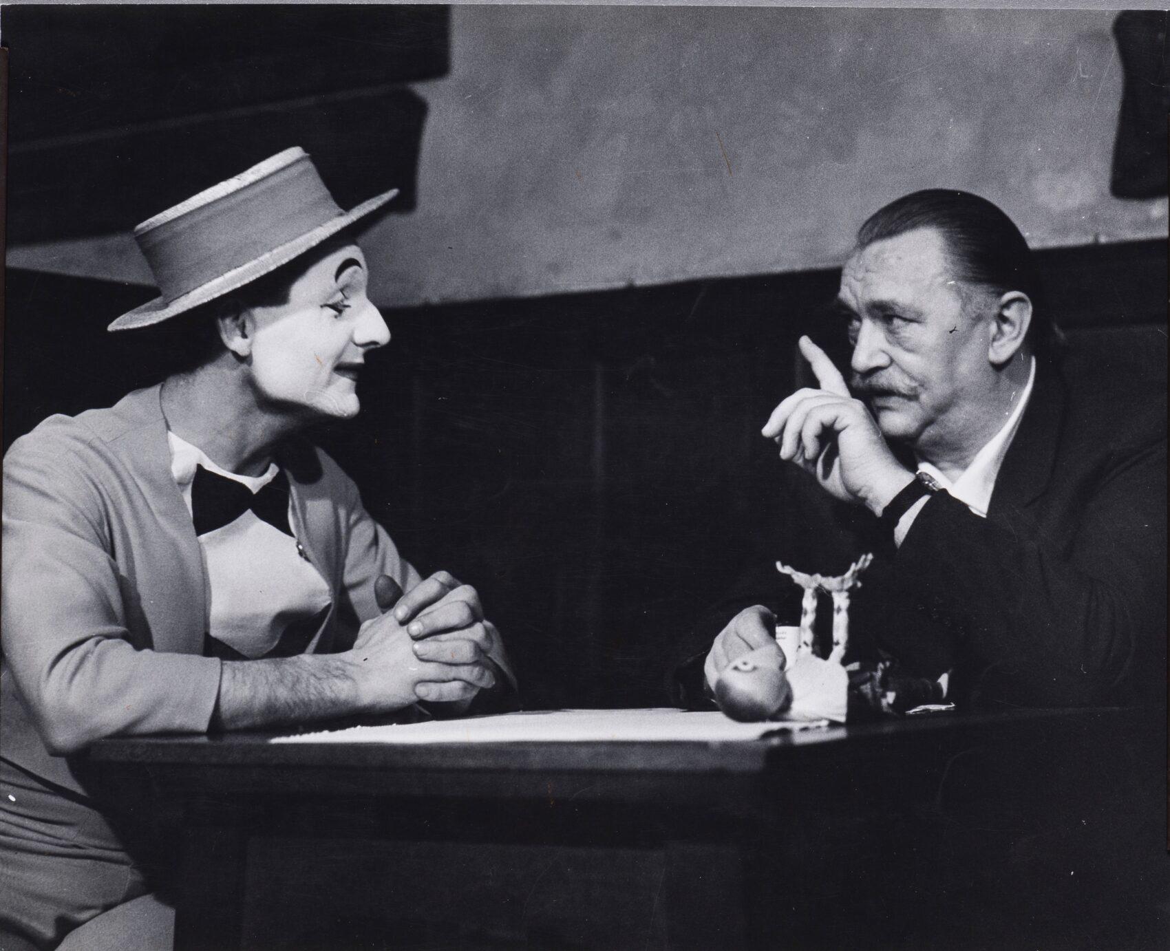 Mim Ladislav Fialka v kostýmu a s typickým bílým líčením naslouchá u stolu Jiřímu Trnkovi. Černobílá fotografie.
