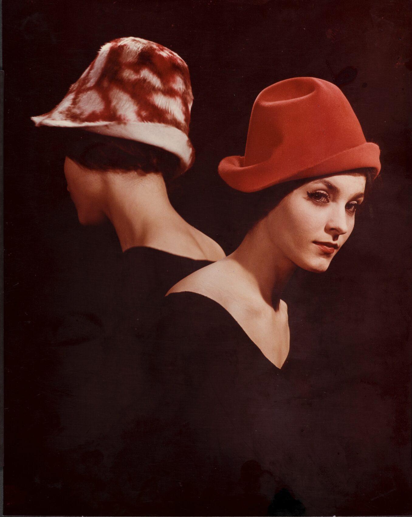 Reklamní fotografie propagující klobouky na hlavách dvou žen, jedna je k objektibu otočena obličejem, jedna zády. Klobouky jsou červené. Barevná fotografie.