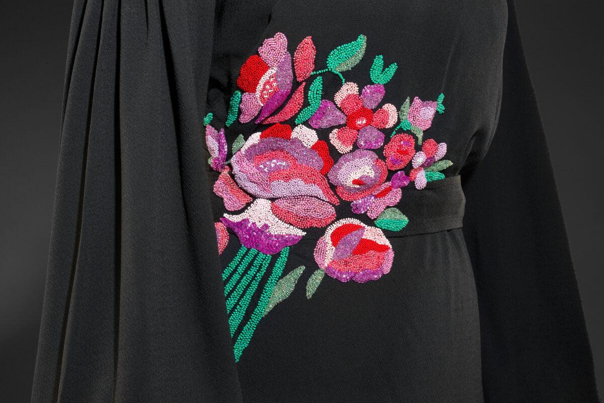 Detail korálky vyšívané kytice v červeno-růžovo-fialovo-zelené barvě.