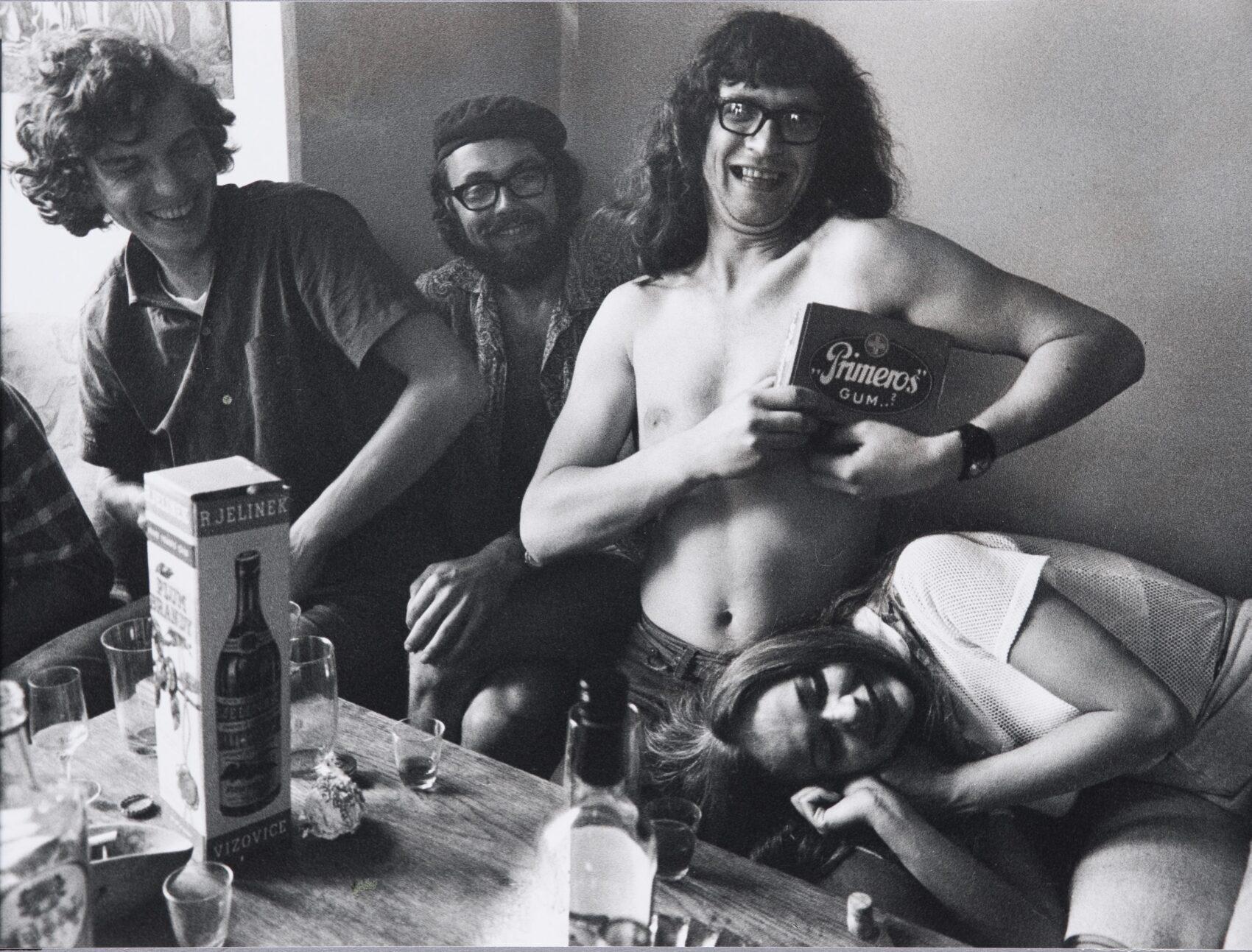 Polonahý Ivan Martin Jirous drží velkou krabici s nápisem Primeros Gum a směje se. Kolem něj přátelé, dva muži a žena