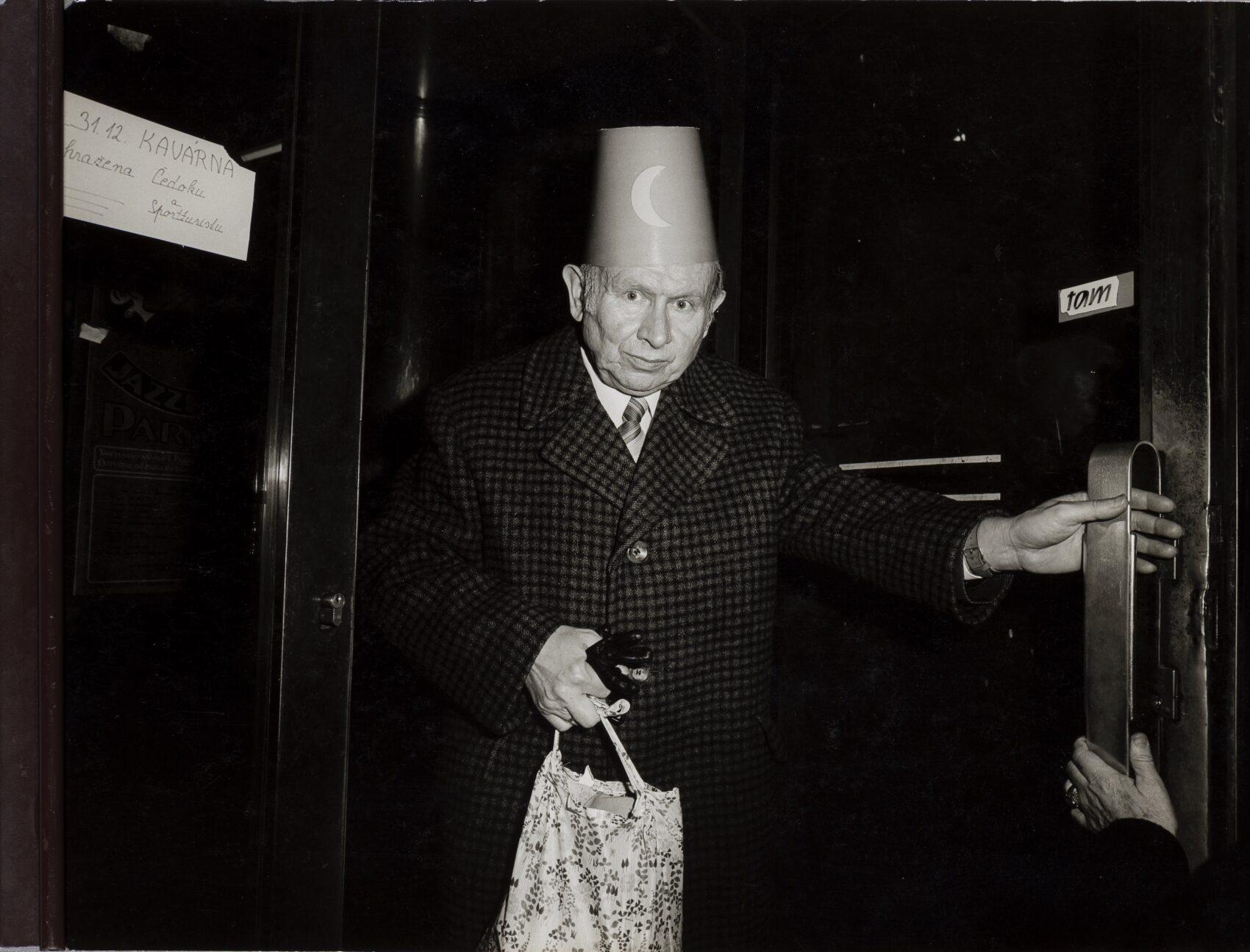 Starší muž s papírovou čepičkou na hlavě a s plátěnou taškou v ruce vychází z nočního podniku