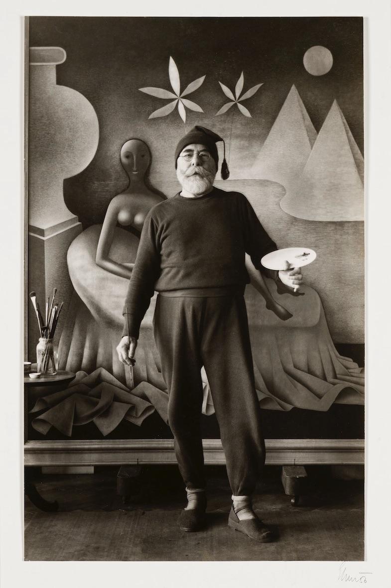 Malíř Jan Zrzavý v čepičce se střapcem a v teplákách, s paletou v ruce stojí před svým nejslavnějším obrazem Kleopatra. Černobílá fotografie