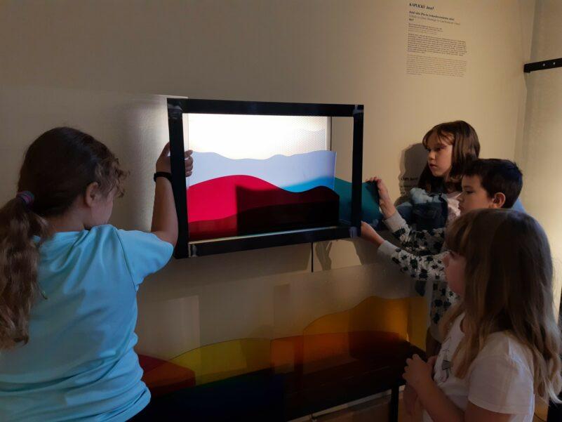 Návštěvníci výstavy vytváří světlenou kompozici z barevných plexiskel