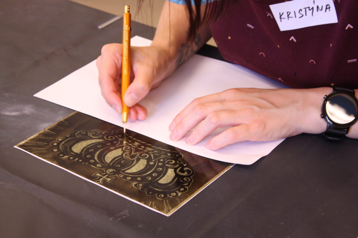 Účastnice kurzu malby na sklo obkresluje obrázek