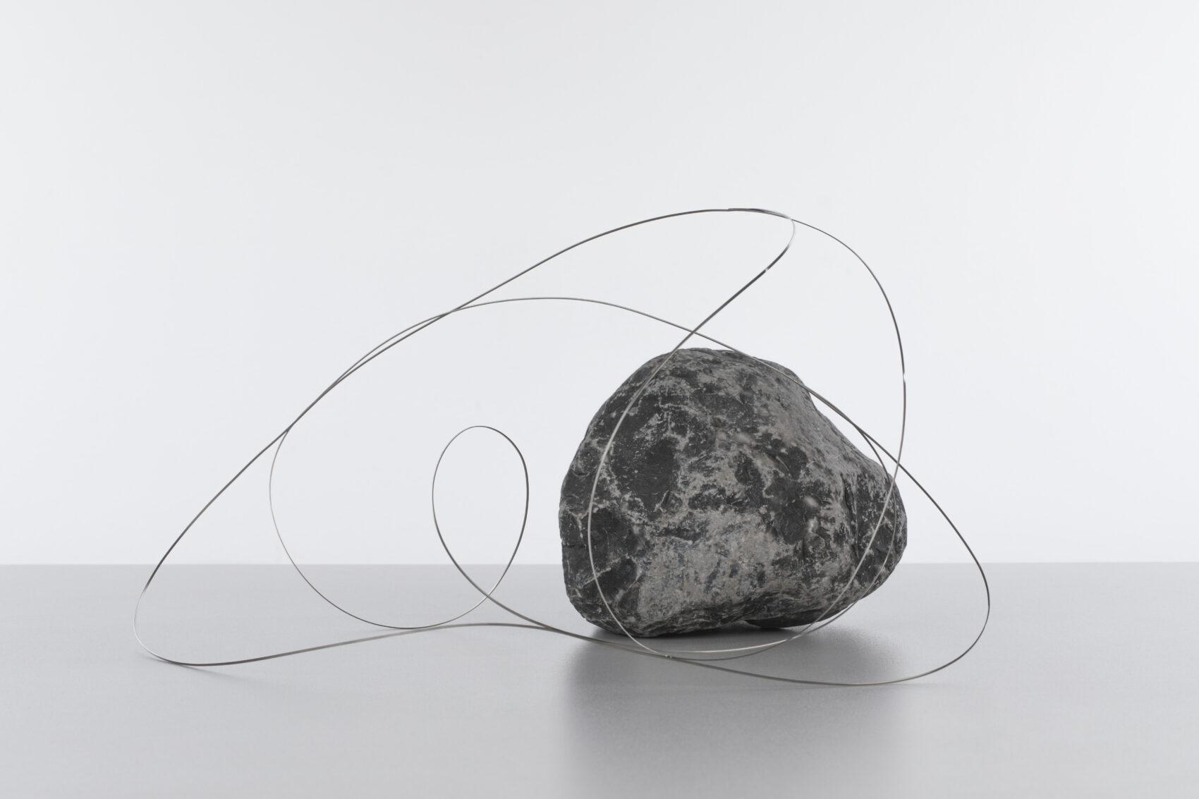 Objekt skládající se z kamenu a tenkého drátu