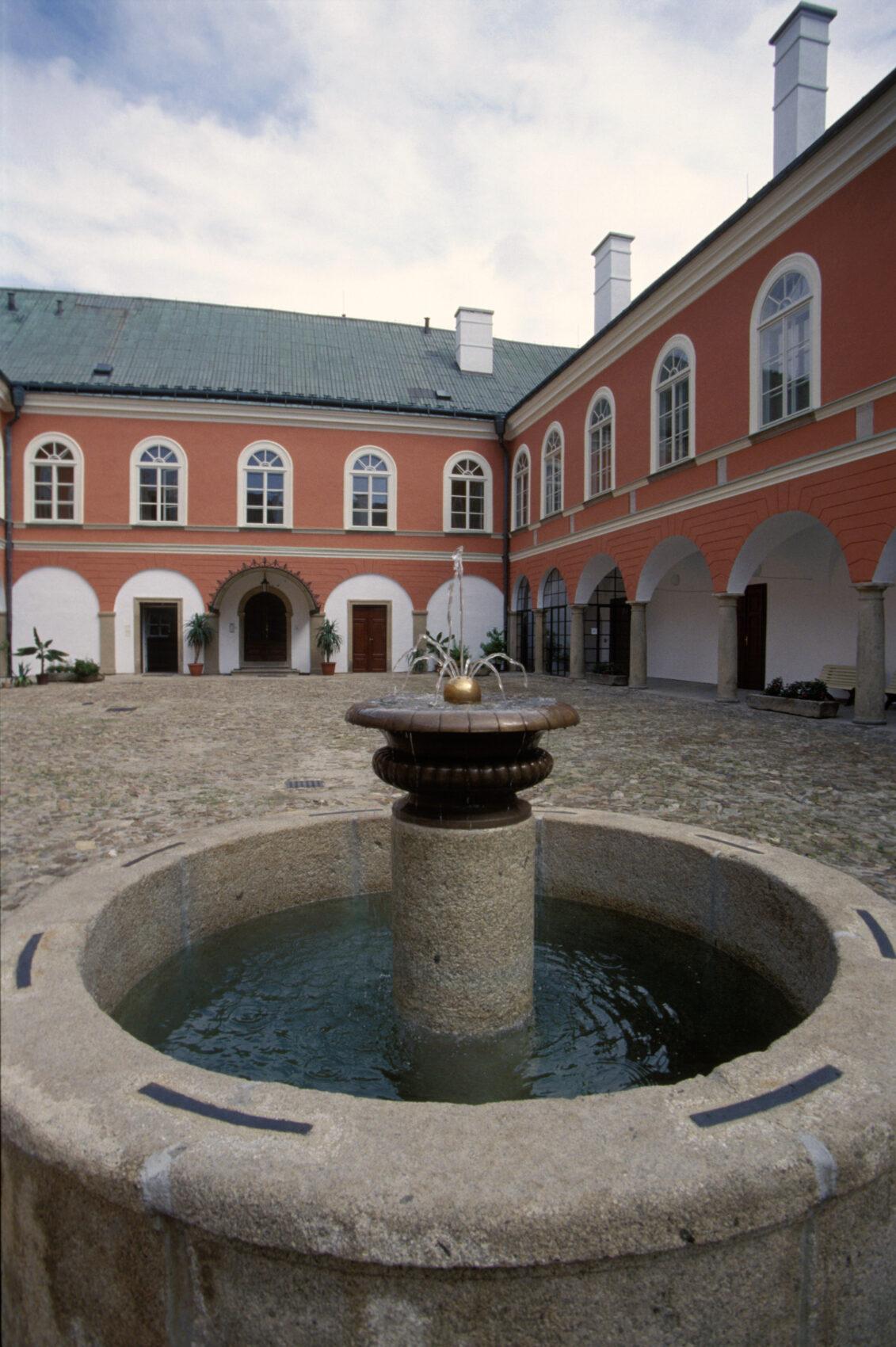 Nádvoří zámku Kamenice nad Lipou s renesančními arkádami a kašnou
