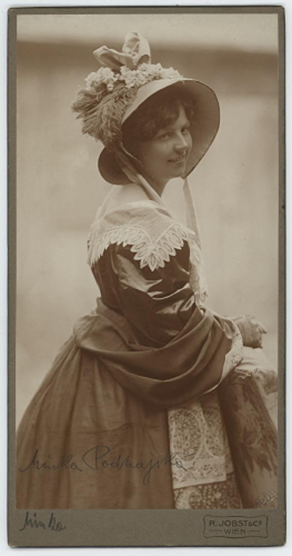 Velmi mladá žena ve zdobeném klobouku a krinolíně