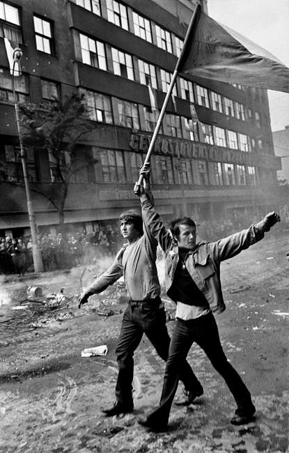 Dva muži s československou vlajkou před hořícím Čs. rozhlasem