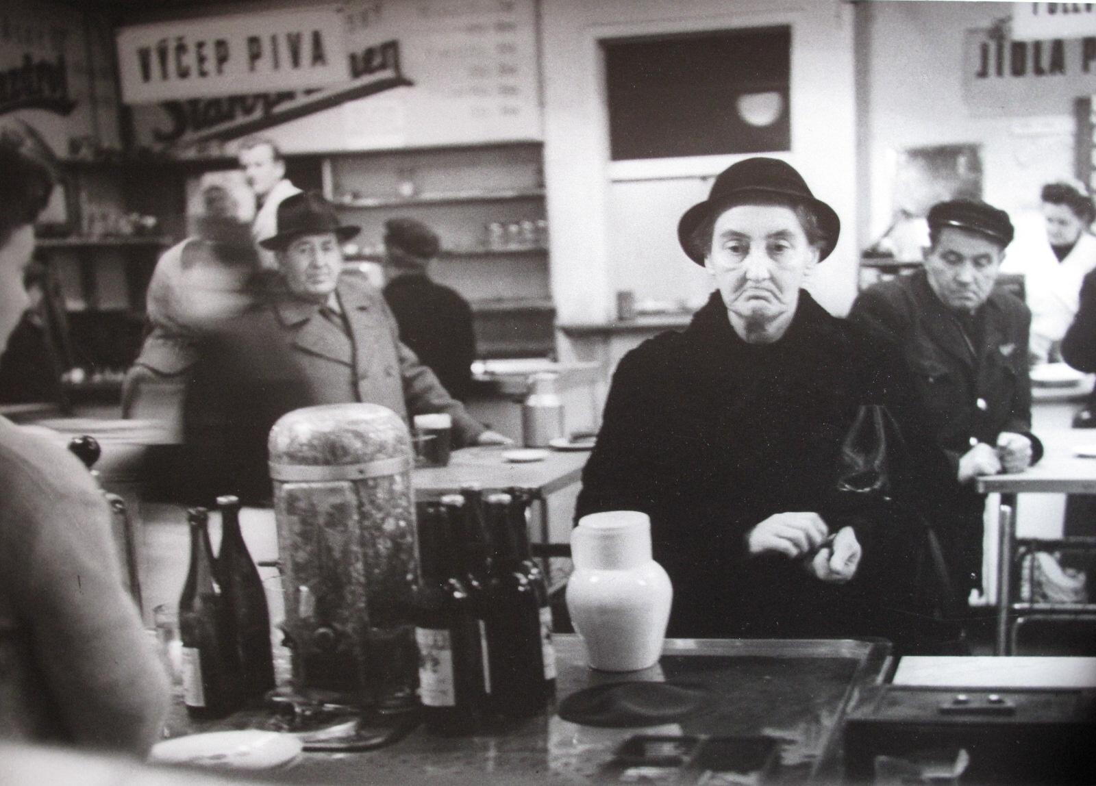 Dobová fotografie z hospody, v centru stará dáma v klobouku