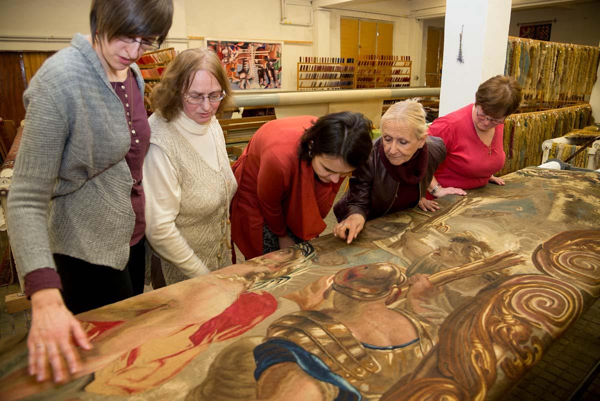 Restaurátorky a odbornice prohlížejí barokní tapiserii