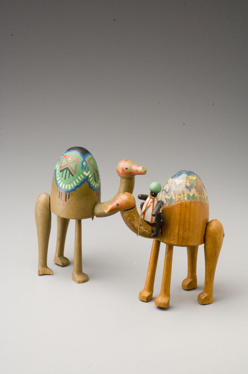 Dvě figurky velbloudů, na jedné z nich sedí panáček