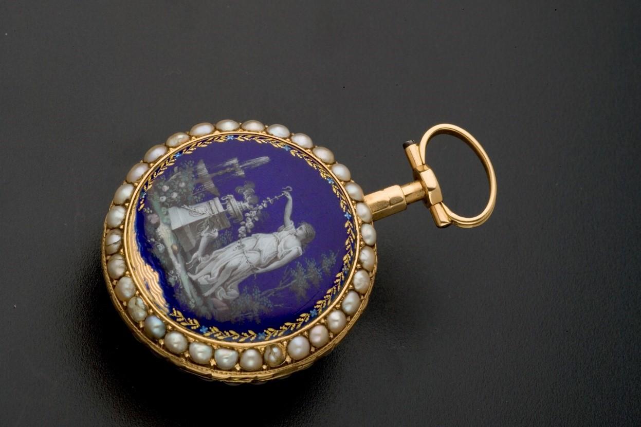 Kapesní hodinky s modrým víčkem s vyobrazením postavy a perlami kolem.
