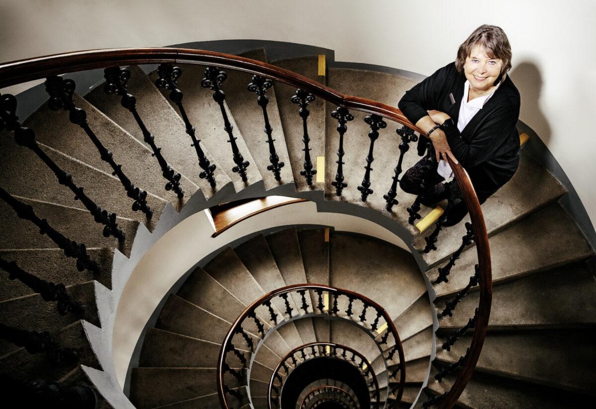 Ředitelka stojí uprostřed kruhového schodiště